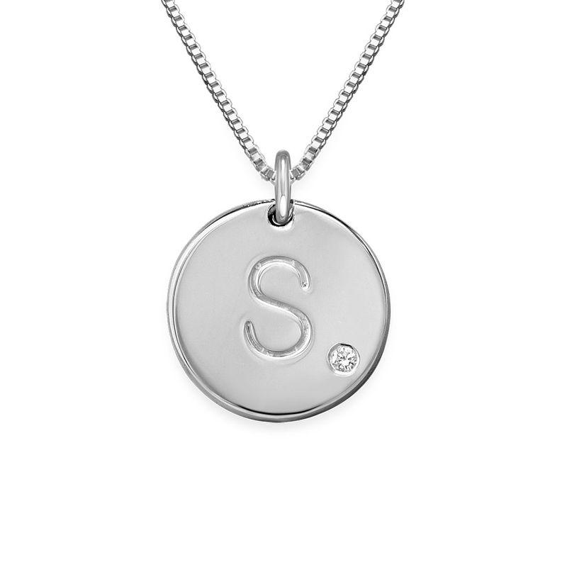 Rundt smykke med bokstav og diamant i sølv