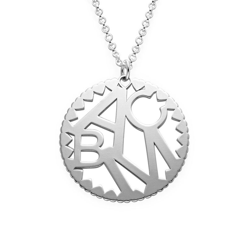 Rundt smykke med bokstaver i sølv