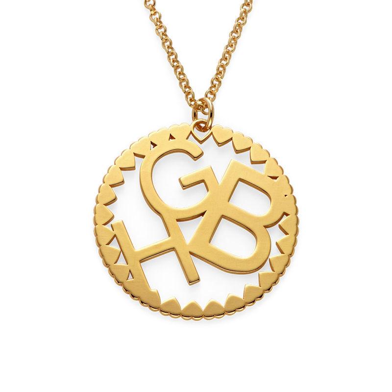 Rundt smykke med bokstaver i gullbelegg
